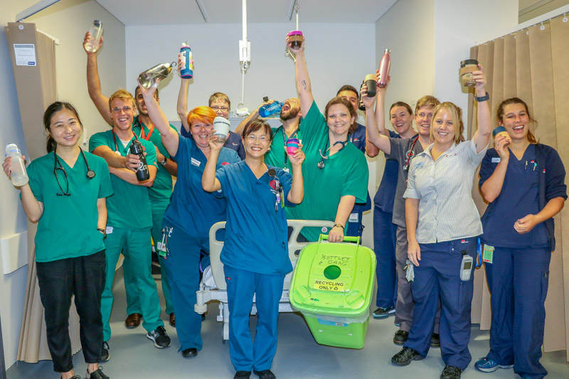 "St George Hospital's ""Green Dragons"" showing off their green bin, Keep Cups and sustainble water bottles"
