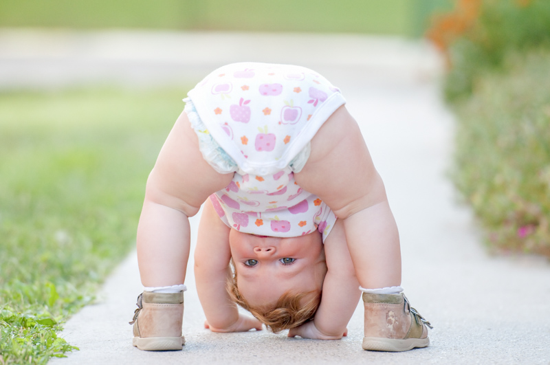 A baby playing upside down on a street