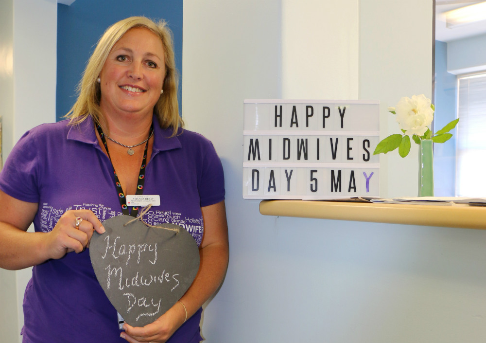 Midwife holding sign saying Happy Midwives Day