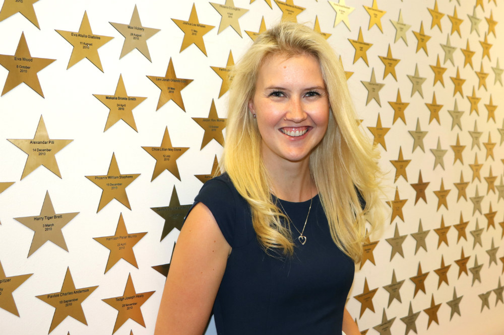 Woman standing in front of wall covered in stars