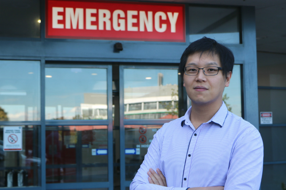 Man standing in front of emergency sign