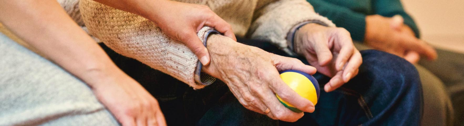 Close up of holding hands a younger person and an older person holding a ball.