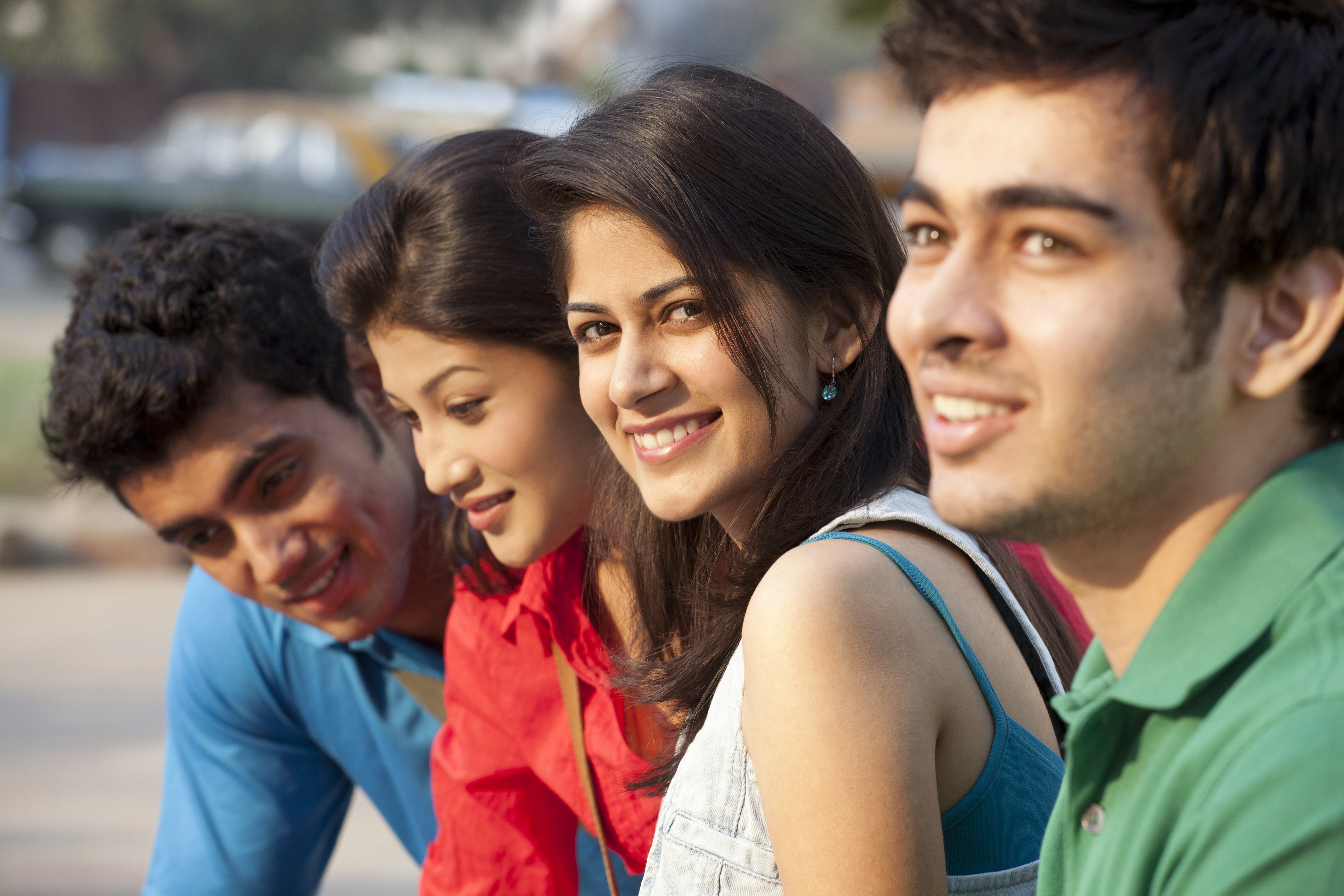 Four young smiling people