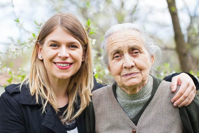 A young woman with her arm around the shoulders of an older woman