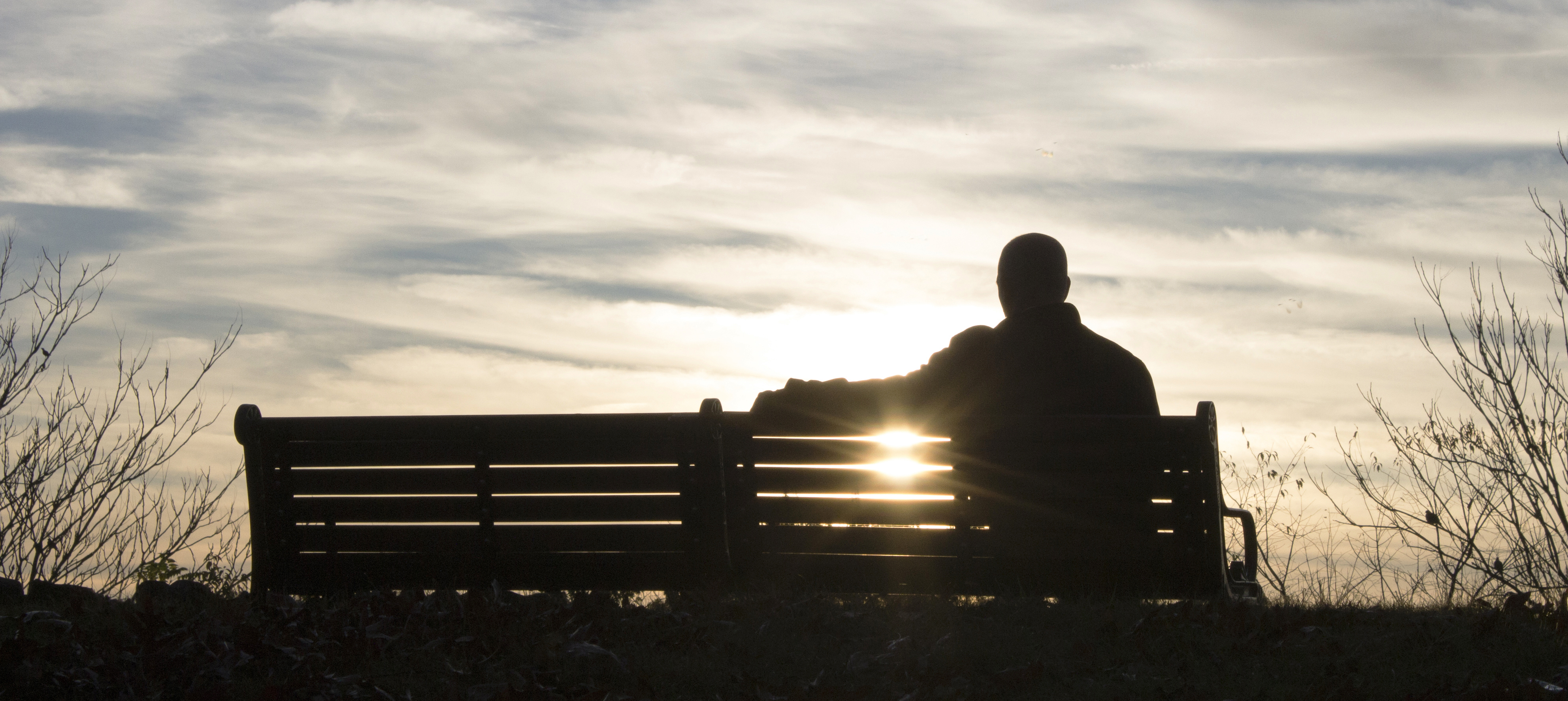 Sillouette of a man sitting on a park bench