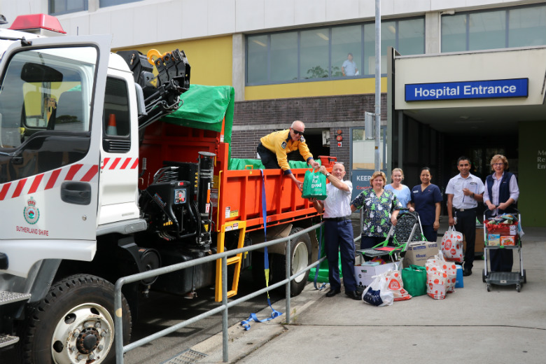 Group of hospital workers standing next to truck with Christmas presents
