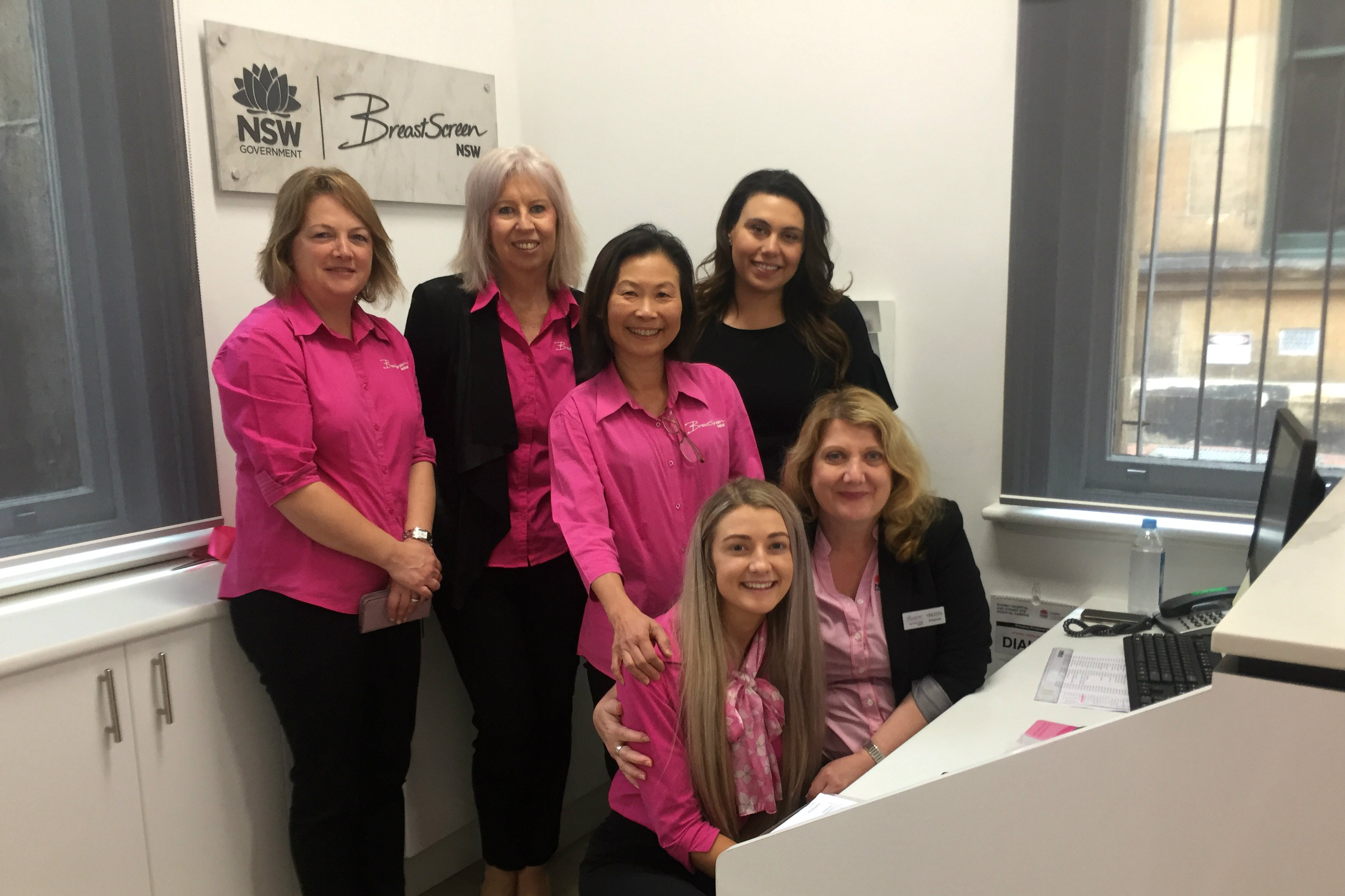 Staff in pink t-shirts at reception desk