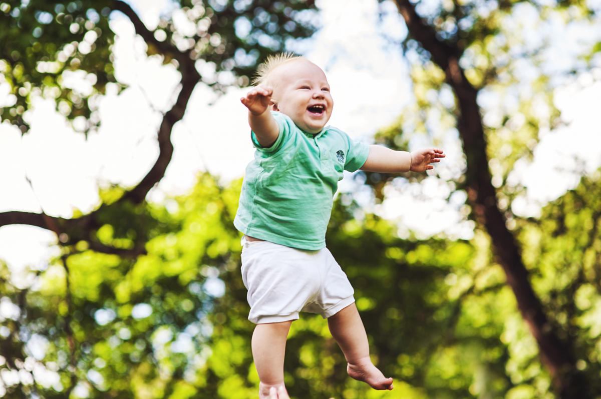 Baby thrown in the air laughing