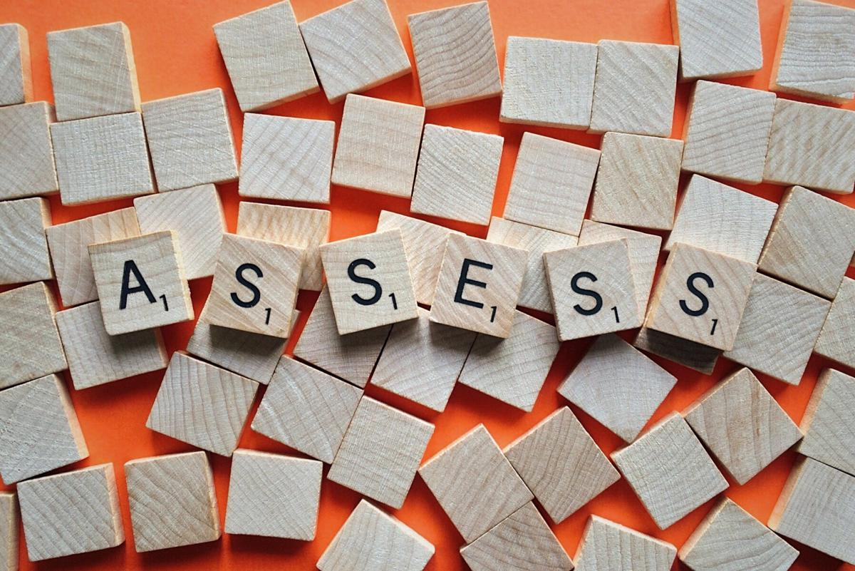 Scrabble tiles spelling out 'assess''