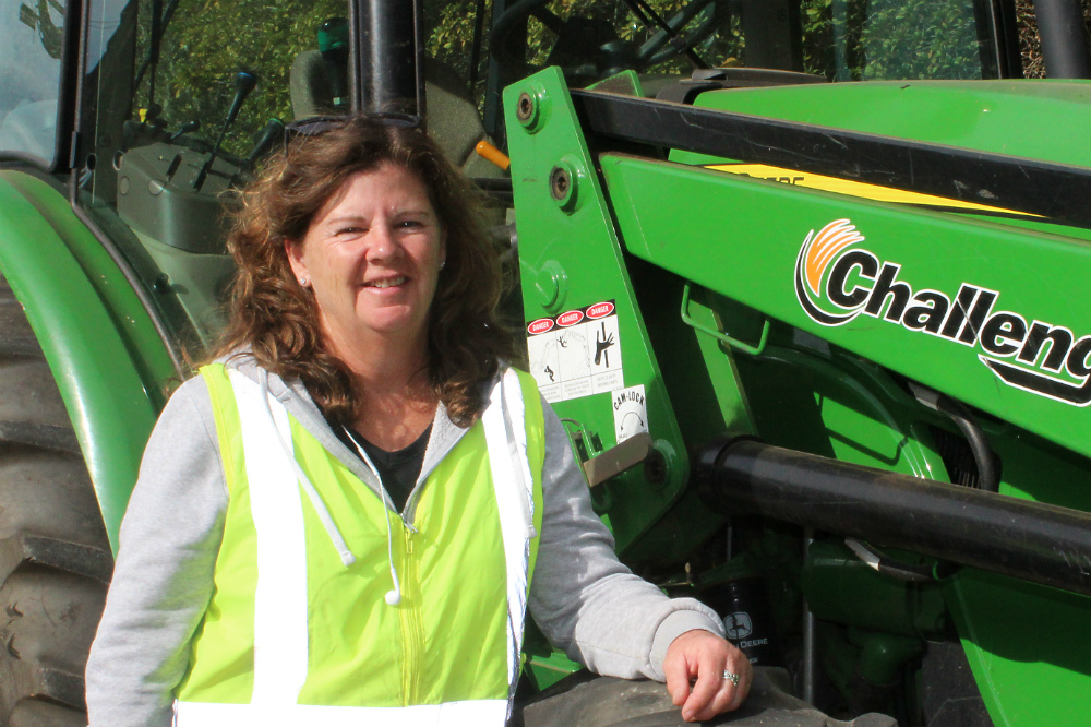 Woman in high vis vest standing in front of tractor