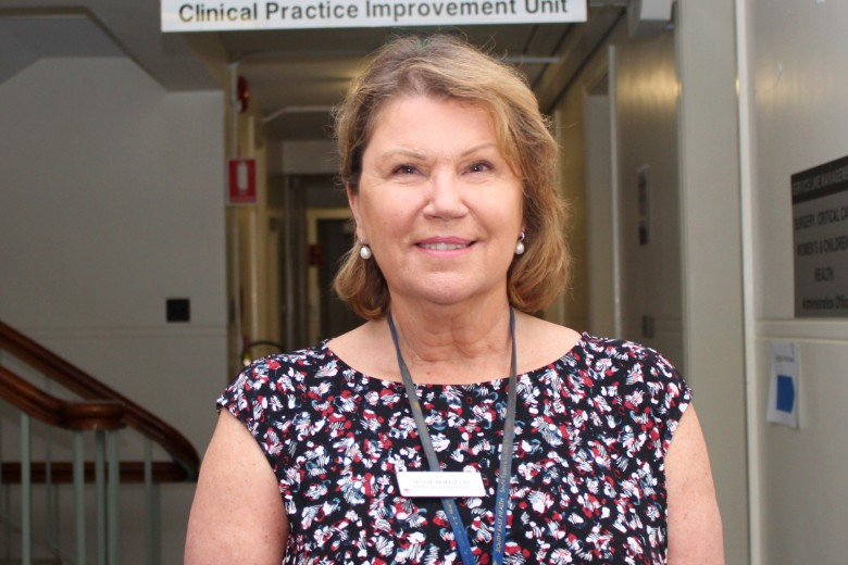 Woman in hallway with sign saying Clinical Practice Improvement Unit