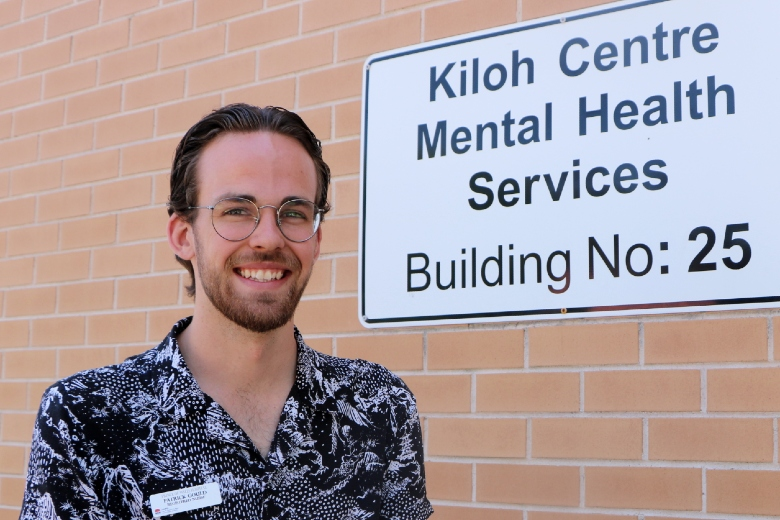 Gentleman standing in front of Mental Health sign at hospital
