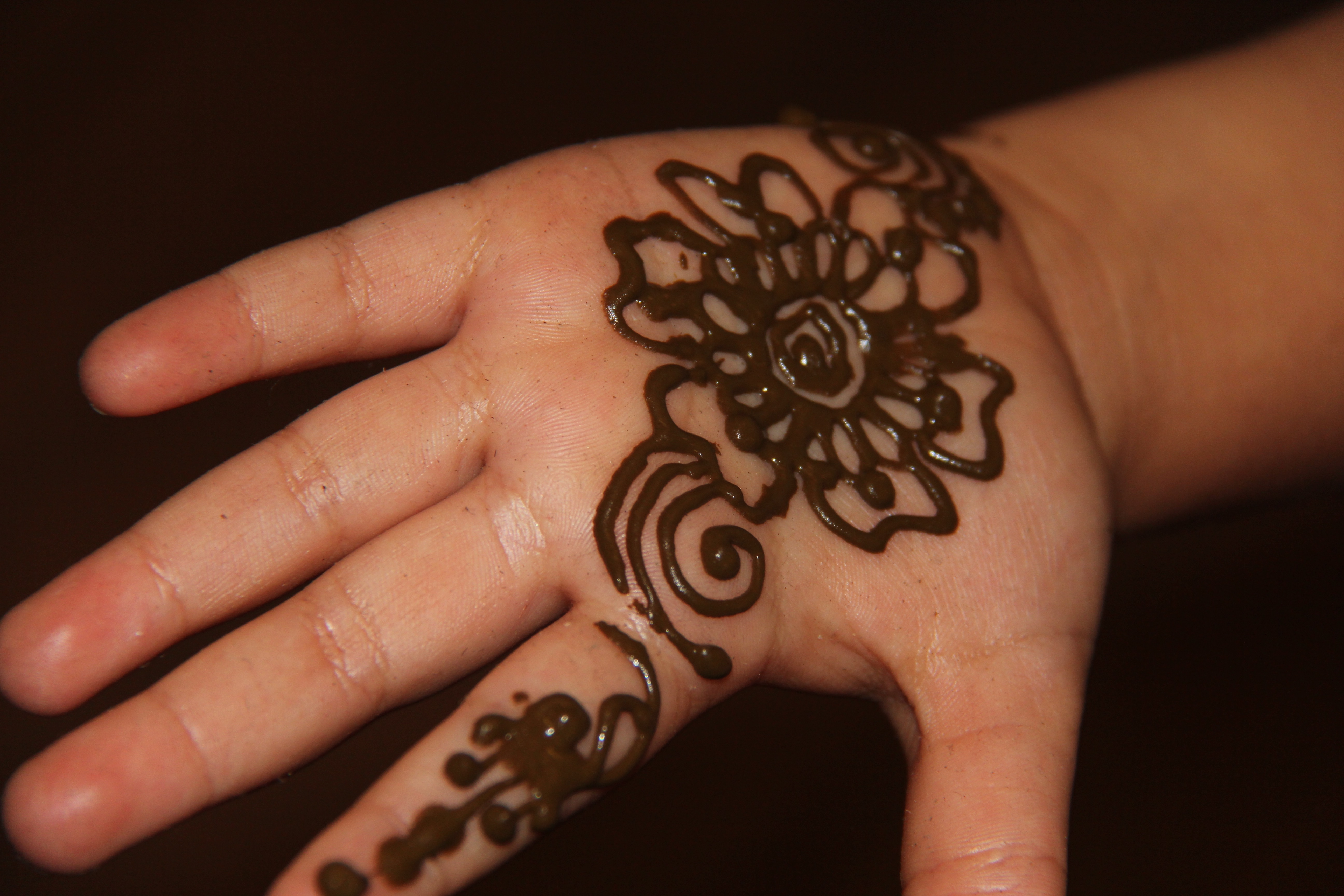A hand covered in henna patterns